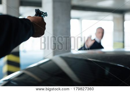 Dangerous weapon. Selective focus of a handgun being targeted at the man while being used by the aggressive criminal