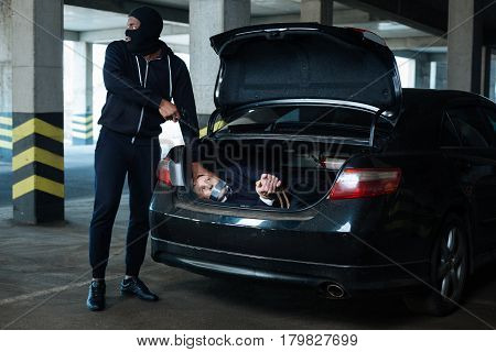Need to hurry. Worried anxious criminal wearing a mask and looking somewhere while pushing a person in the car boot