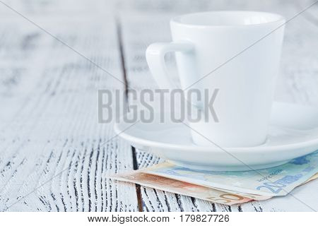 Cup Of Coffee Euro Bill And On Wooden Table. Payment, Tip
