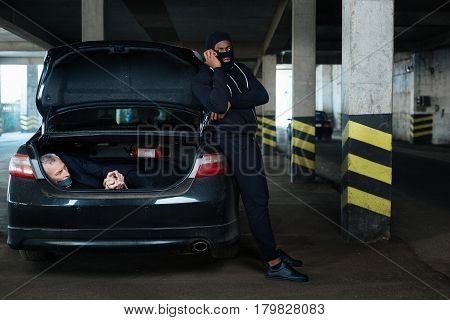Being a guardian. Dangerous aggressive well built man leaning on the car and holding a gun while guarding his hostage