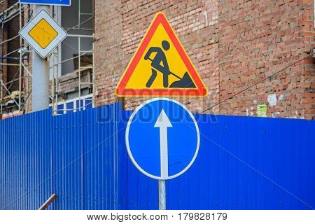 Close up road works and blue go straight signs with main road sign in background