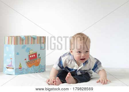 Crying baby boy with a gift package. Sad infant in hysterics