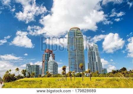 Miami high residential buildings hotel or houses in south beach sunny summer outdoor with green grass palm trees and cloudy blue sky. modern architecture in megalopolis. business tourism and wanderlust