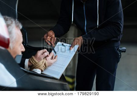 Sign this. Unhappy sad serious man having his hands tied and being forced to sign a document while being kidnapped