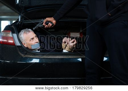 My life is in danger. Handsome grey headed unhappy man having his hands tied and having adhesive type over his mouth while being in the car boot