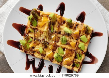 Delicious waffle with fruits and syrup on white plate, close up