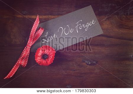 Red Poppy On Suit Jacket On Dark Wood Background.