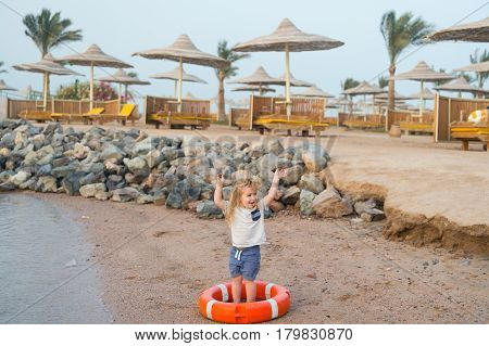 Small Baby Boy With Happy Face With Lifebelt On Beach