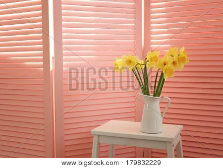 Bouquet of beautiful narcissus flowers on folding screen background