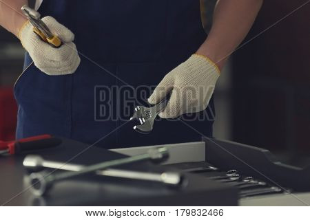 Auto mechanic selecting tools in car repair shop, closeup