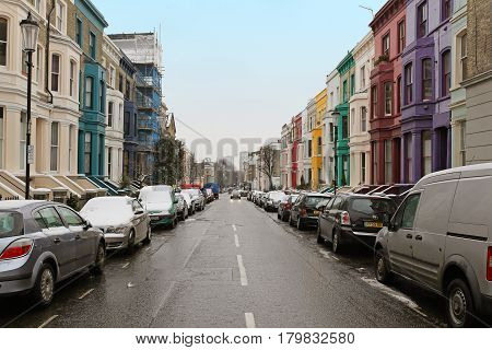 LONDON UNITED KINGDOM - January 19; Street with colurful houses and cars under snow during winter in London United Kingdom - January 19 2013; Street on Notting Hill during winter with parked cars in London