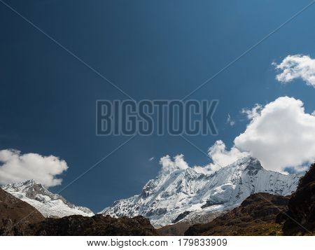 Peak of the snowcapped Chacraraju mountain in the Cordillera Blanca, Peru, over a blue sky with some clouds. Lots of copyspace.