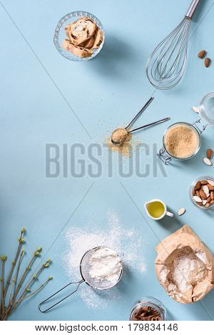 Cooking and baking ingredients - egg, flour, brown sugar, almonds over blue table. Spring theme. Top view, copy space, flat lay.