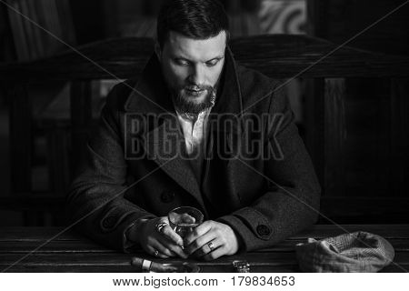 A young bearded man dressed in a vintage style drinks whiskey in a pub Black-and-white