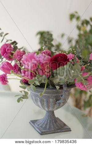 Pink Ranunculus Flower And Pink Tulips Arranged In Iron Vase