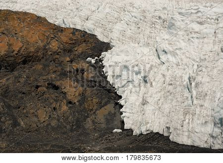 The border between the ice of a shrinking glacier and the rock of a mountain, symbolizing climate change and global warming.