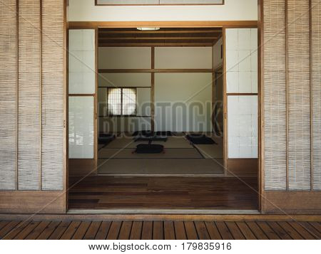 Photography of the entrance sliding doors of an empty Japanese tea room with some pillows on the ground.