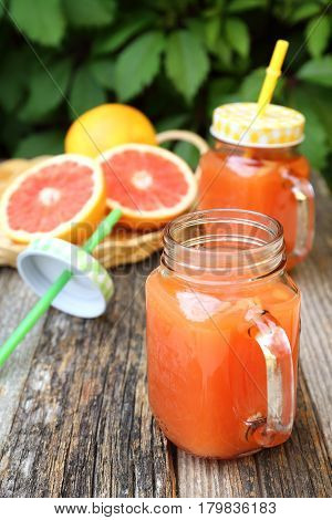 Grapefruit juice in two glass mugs and grapefruit halves in wicker basket