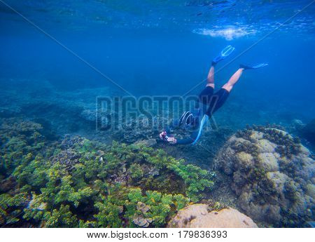 Snorkeling man in snorkeling mask. Photography underwater. Snorkel in tropical lagoon undersea photo. Summer holiday activity. Water sport in open sea. Exploring tropical coral reef. Man on vacation
