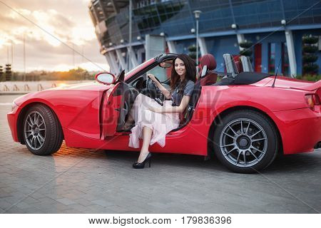Pretty Young Brunette Woman Sitting At Luxury Red Cabriolet Car At The Sunset.