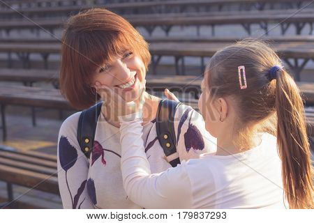 Girl daughter tells mom to smile. The sun is shining at sunset. Mom is smiling. Daughter corrects mom's smile.