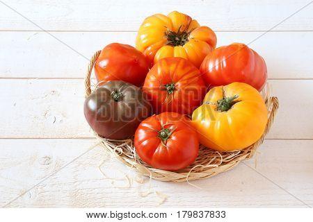 Assortment of Ripe Bullish heart tomatoes in wicker basket