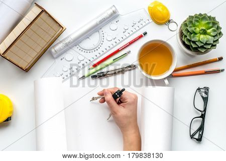 Construction office with architect working tools, hands and cup on white table background top view