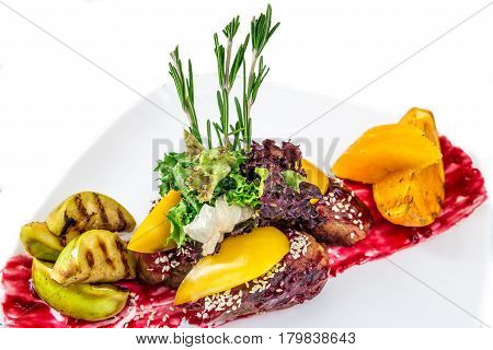 Meat with vegetables apples and oranges on a white plate