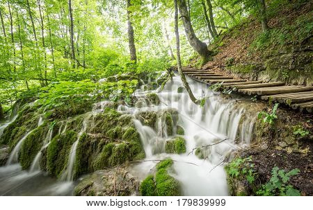 The sunlight filters through the trees in Plitvice Lakes National Park, as the water cascades over the rocks alongside an elevated wooden walkway.