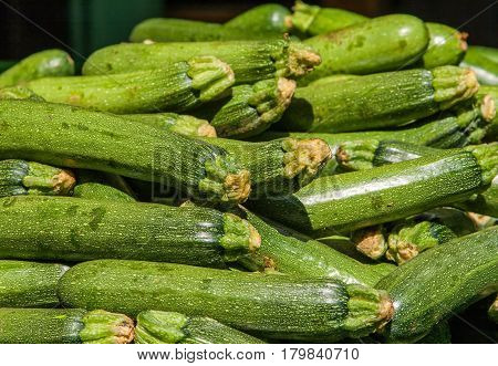 Food background: fresh zucchinis or courgettes from the market