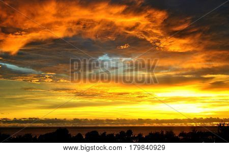 Tongues of Fire -Tongues of fire in the clouds as the sun sets in Saipan, Northern Mariana Islands