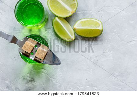 green absinthe with sugar cubes in spoon on stone table background top view mockup