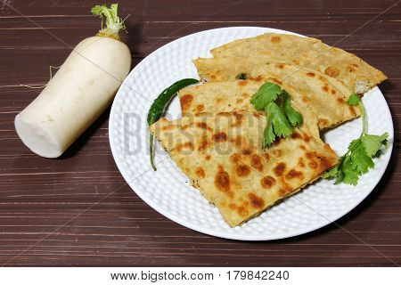 Healthy Indian Mooli or Radish paratha or stuffed flatbread with coriander and green chilies on wooden background