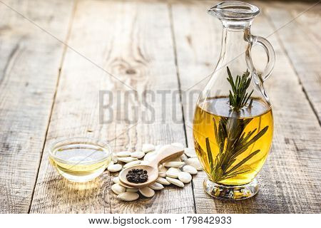 extra oil in carafe with pepitas and fresh rosemary on wooden desk background mock-up