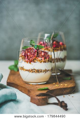 Healthy breakfast. Greek yogurt, granola, blood orange layered parfait in glasses with fresh mint on wooden board, grey concrete wall at background, copy space. Clean eating, weight loss, food concept