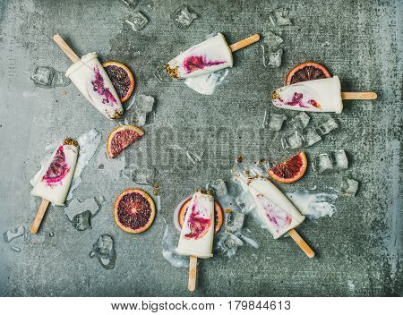 Healthy summer dessert. Blood orange, yogurt and granola popsicles on ice cubes over grey concrete background, top view, copy space. Clean eating, dieting, weight loss concept