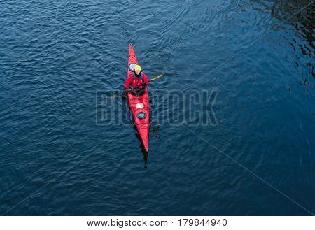 woman paddles a white kayak on the river near the shore, kayaking