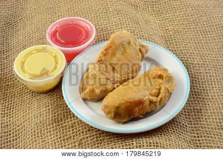 Fried chicken tenderloin appetizer with mustard and sweet and sour sauce