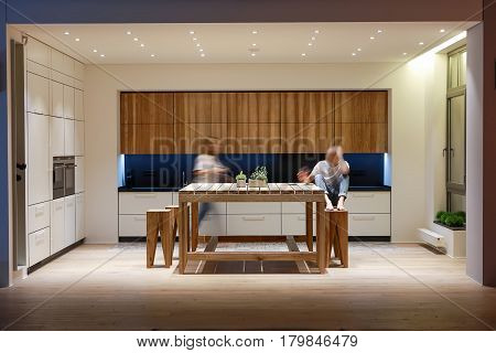 Glowing kitchen in modern style with a parquet and tiles on the floor. There is a wooden table with plants in the pots and stools, oven. Behind the table there is a dark tabletop with sink and knives.
