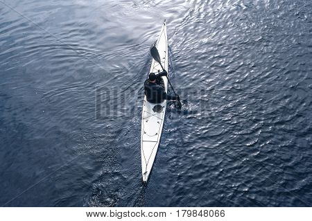 man paddles a white kayak on the river near the shore, kayaking