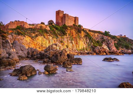 Talamone rock beach and medieval fortress Rocca Aldobrandesca and walls at sunset. Maremma Argentario Italian travel destination. Tuscany Italy.