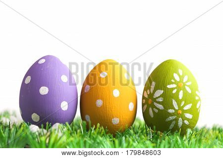 Bunch of easter eggs in pastel colors on grass, isolated on white background