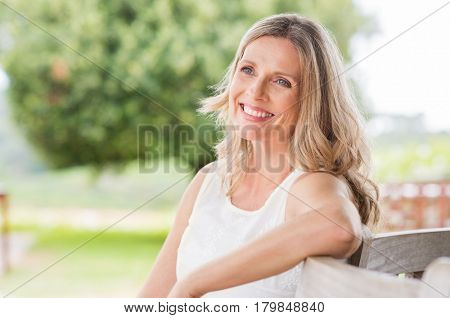 Happy blonde mature woman sitting outdoor and thinking. Senior woman relaxing on a wooden bench under the tree in a summer day. Portrait of middle aged woman smiling and daydreaming.