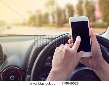 Woman driving and using smartphone on the road Concept of smartphone addiction phubbing or social network issues