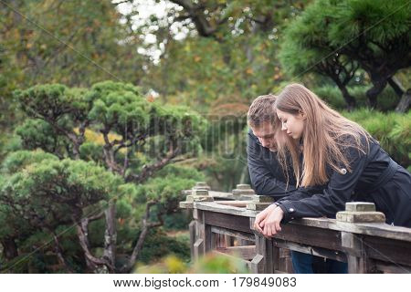 Young romantic couple together outside, talking on wooden bridge in Japanese garden, looking down