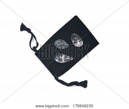 Tumbled clear quartz on black velveteen crystal pouch isolated on white background