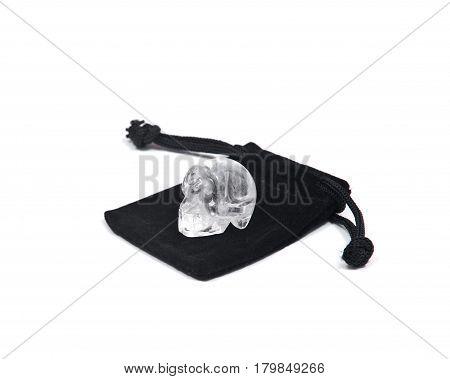 Clear quartz mini skull on black velveteen crystal pouch isolated on white background