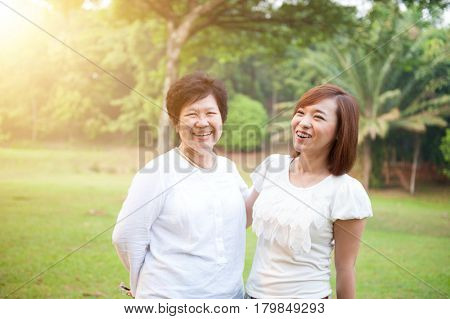 Portrait of Asian elderly mother and daughter talking, senior adult woman and grown child. Outdoors family at nature park with beautiful sun flare.