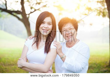 Portrait of beautiful Asian elderly mother and daughter, senior adult woman and grown child. Outdoors family at nature park with beautiful sun flare.