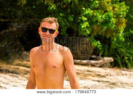 Handsome man on sunny beach. Smiling man in black sunglasses on white sand beach. Summer holiday banner template. Green tree and white sand of tropical island. Exotic vacation view. Beach day photo